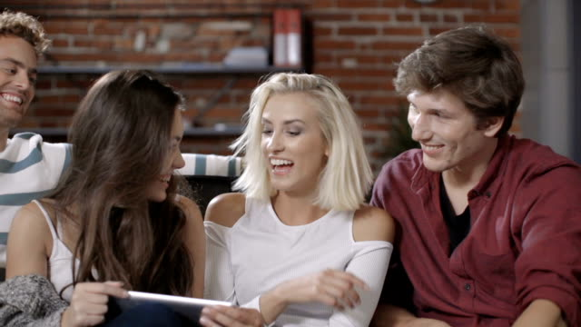 Group of happy young friends sitting on a sofa and using tablet computer. video