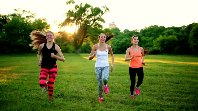 group of healthy girls running outdoors at sunset with lens flare video
