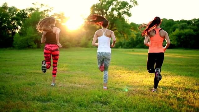 group of healthy girls running outdoors at sunset with lens flare group of healthy girls running outdoors at sunset with lens flare bodyweight training stock videos & royalty-free footage