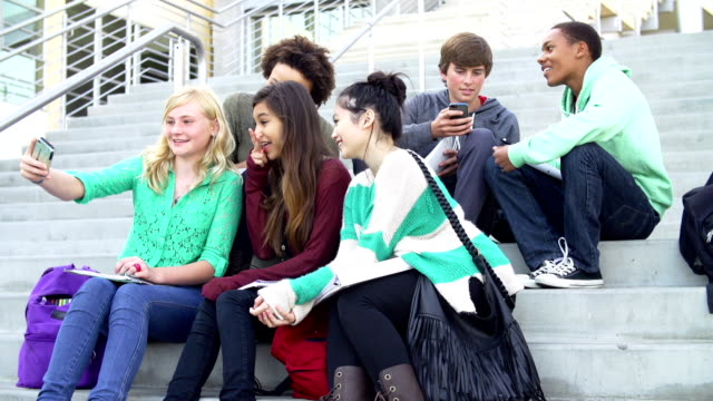 Group Of High School Students Sitting Outside Building video