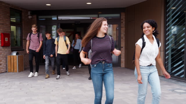 Group Of High School Students Walking Out Of College Building Together Front view of two female high school students walking out of school building with fellow students - shot in slow motion student stock videos & royalty-free footage