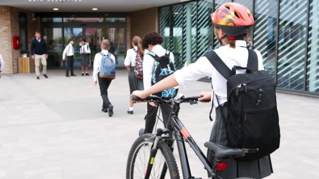 Grupo de estudiantes de secundaria con uniforme al llegar a la escuela, caminar o montar en bici - vídeo