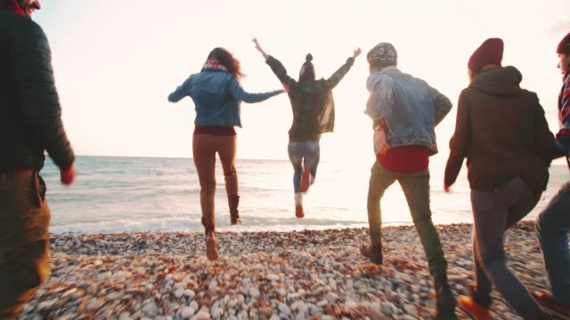 group of hipsters jumping on the beach and having fun - copricapo abbigliamento video stock e b–roll
