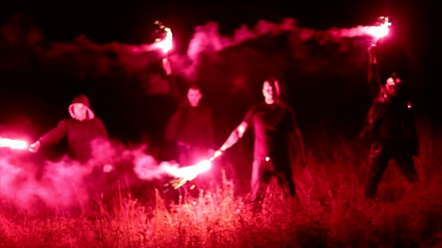 Group of hooligans holding torches at night Group of hooligans holding torches in the field at night flare stack stock videos & royalty-free footage