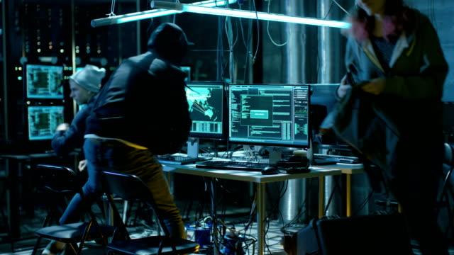 Grupo de Hackers internacional quería ejecutar desde de ellos están roto escondite. Lugar tiene muchas pantallas y Cables, neón oscuro. - vídeo