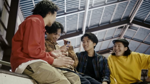 Group of Japanese boys watching video on smart phone