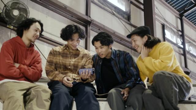 vidéos et rushes de groupe de garçons japonais regardant la vidéo sur le téléphone intelligent (mouvement lent) - culture des jeunes