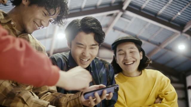 vidéos et rushes de groupe de garçons japonais regardant la vidéo sur le téléphone intelligent (mouvement lent) - seulement des japonais