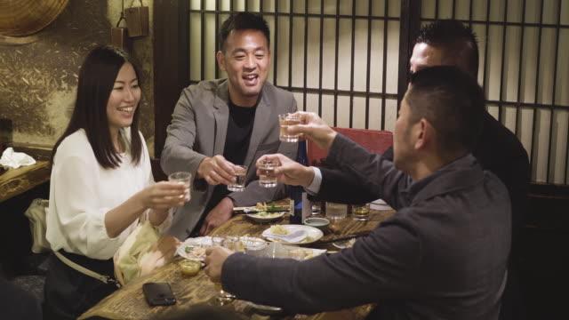 東京レストランで祝う日本人同僚のグループ - 飲み会点の映像素材/bロール