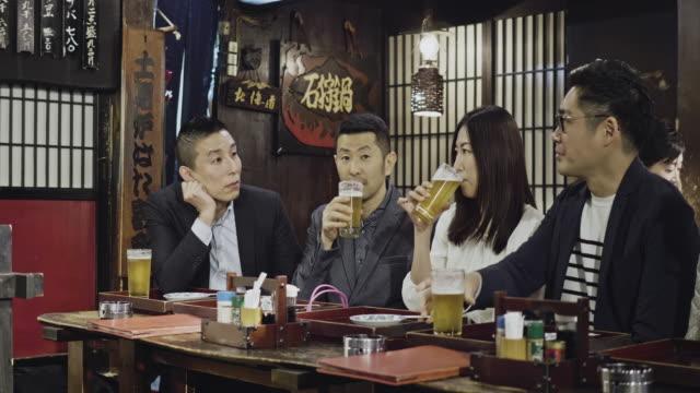 居酒屋でビールを食べている日本人グループ - ビール点の映像素材/bロール