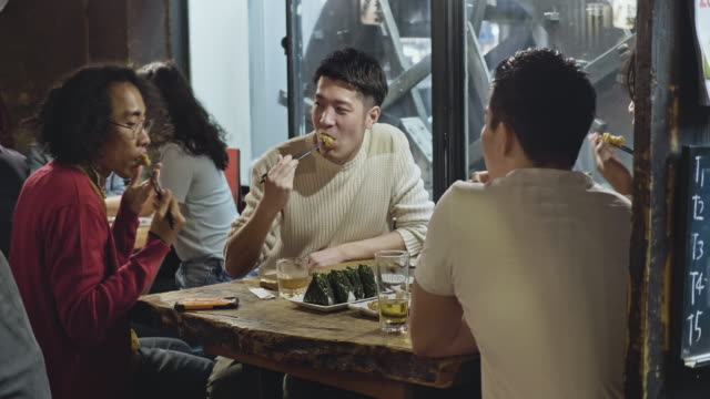 group of japanese young people enjoying dinner at tokyo restaurant - bar lokal gastronomiczny filmów i materiałów b-roll