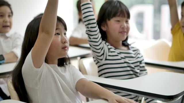 stockvideo's en b-roll-footage met groep van vrolijke aziatische elementaire studenten die hun armen opvoeden om een vraag te beantwoorden van leraar in classroom. kleuterschool pre school concept. - kindertijd