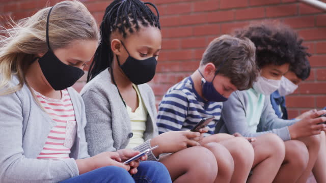 Group of kids wearing face masks using smartphones while sitting together