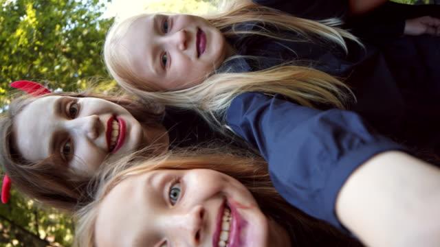 grupa dzieci noszących kostiumy halloweenowe robiąc selfie - four seasons filmów i materiałów b-roll