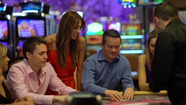 Group of latin american players at the blackjack table looking focused
