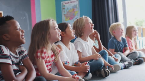 Group Of Laughing Elementary School Pupils Sitting On Floor Listening To Teacher Multi-cultural group of elementary school pupils sitting in a line on floor in classroom listening to teacher and laughing - shot in slow motion child stock videos & royalty-free footage
