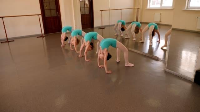gruppe von kleinen mädchen machen eine strecke in einem tanzstudio. ballett für kinder - ballettröckchen stock-videos und b-roll-filmmaterial