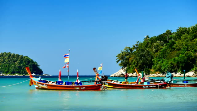 Group of Long-tail boats converted boat excursions In order to serve tourists cruising the island of Andaman Sea coast beaches on a sunny day and the good weather in travel and transportation concept video