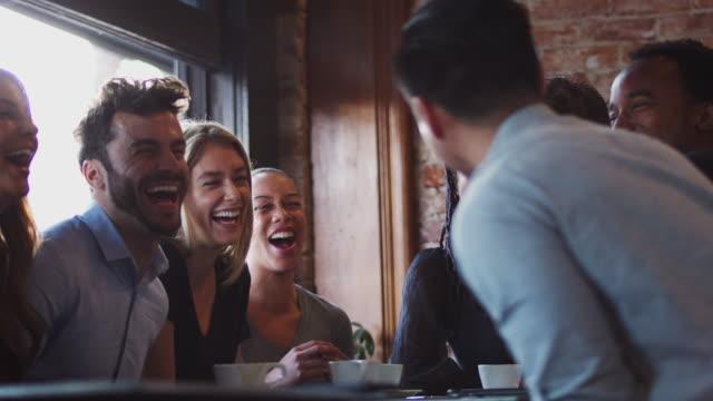 gruppe von männlichen und weiblichen freunden treffen sich zum kaffee sitzen am tisch zusammen - freund stock-videos und b-roll-filmmaterial