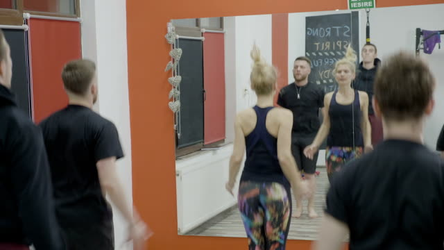 Group of male coworkers jumping and doing aerobic class together with their female manager at the gym as part of the team building program video