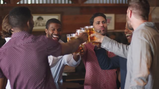 group of male friends on night out for bachelor party in bar making toast together - bachelor party stock videos and b-roll footage