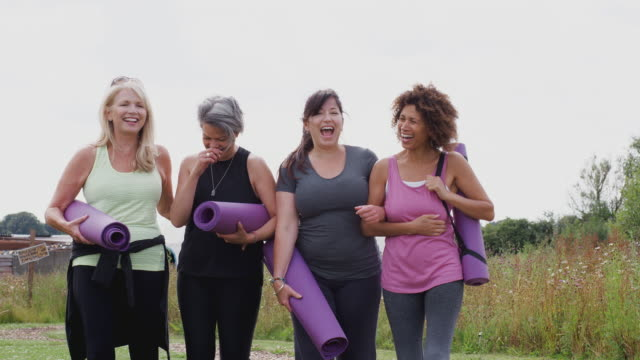 Group Of Mature Female Friends On Outdoor Yoga Retreat Walking Along Path Through Campsite video