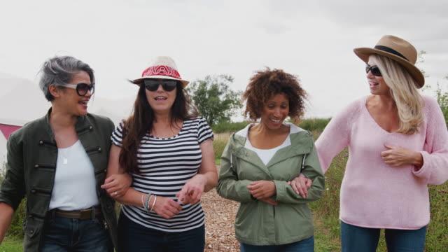 group of mature female friends walking along path through yurt campsite - amicizia tra donne video stock e b–roll