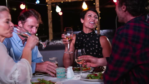 Group Of Mature Friends Enjoying Meal At Rooftop Restaurant Group of mature friends enjoying meal at outdoor restaurant together.Shot in 4k on Sony FS700 at frame rate of 25fps medium shot stock videos & royalty-free footage
