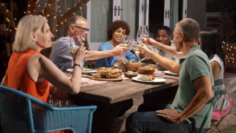 gruppo di amici maturi che si godono il pasto all'aperto nel cortile di casa - piano americano video stock e b–roll