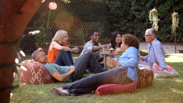 Group Of Mature Friends Enjoying Picnic In Backyard Together video