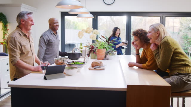 gruppo di amici maturi che si incontrano a casa preparando il pasto e facendo un brindisi con il vino insieme - girato al rallentatore - relazione umana video stock e b–roll