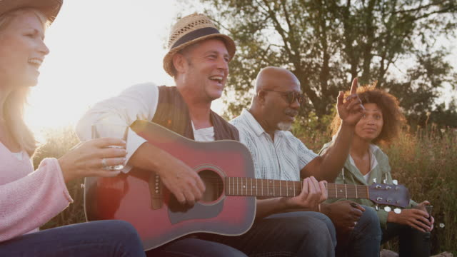 Group Of Mature Friends Sitting Around Fire As They Drink And Sing Songs At Outdoor Campsite Group of mature friends sitting outdoors around fire drinking and singing songs at campsite against flaring sun - shot in slow motion mature adult stock videos & royalty-free footage