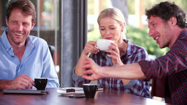 Grupo de amigos maduros sentado en una cafetería charlar - vídeo