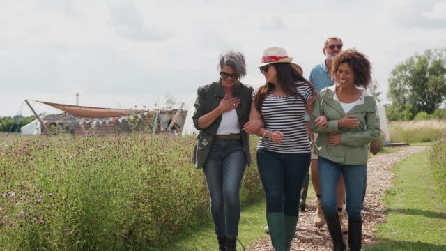 Group Of Mature Friends Walking Along Path Through Yurt Campsite - vídeo