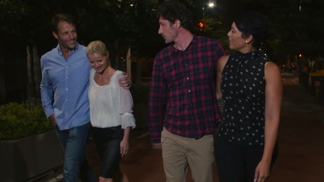 Group Of Mature Friends Walking Along Street On Night Out video