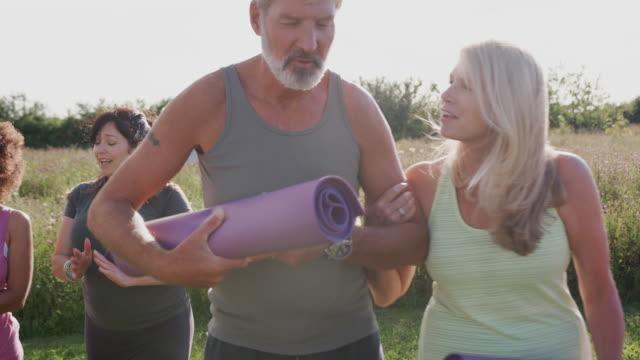 야외 요가 수업의 끝에 운동 매트와 성숙한 남자와 여자의 그룹 - mindfulness 스톡 비디오 및 b-롤 화면