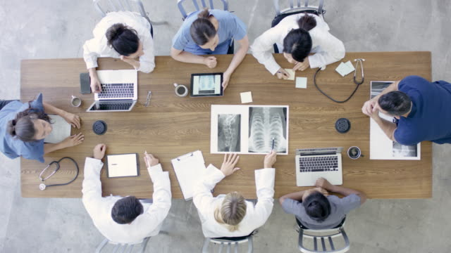 Video Group Of Medical Professionals Sitting Around Table In Meeting