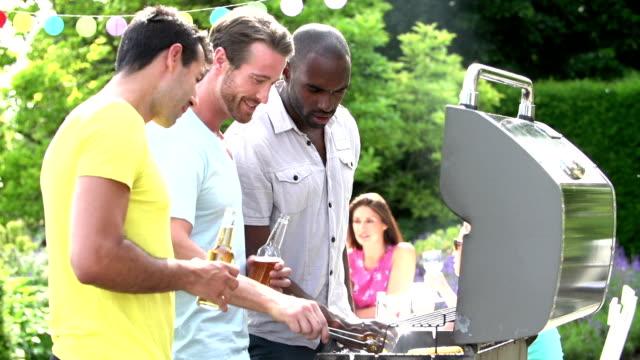 Grupo de hombres en la cocina a la parrilla en su casa - vídeo