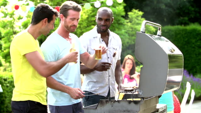 Group Of Men Cooking On Barbeque At Home video