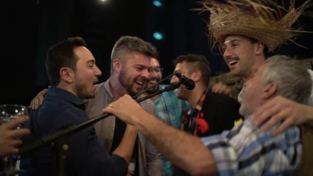 grupa mężczyzn ubranych w czerwcowy strój imprezowy i śpiewających podczas imprezy junina - tradycja filmów i materiałów b-roll
