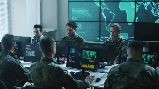 Group of Military IT Professionals on Briefing in Monitoring Room Filled with Displays on Military Base