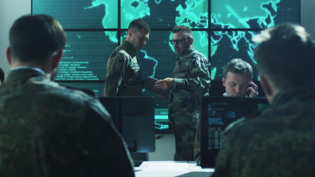 Group of Military IT Professionals on Briefing in Monitoring Room Filled with Displays on Military Base Group of Military IT Professionals on Briefing in Monitoring Room Filled with Displays on Military Base. Shot on RED Cinema Camera in 4K (UHD). army stock videos & royalty-free footage