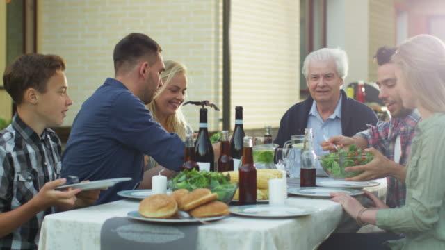 vídeos y material grabado en eventos de stock de grupo de gente de raza mixta divirtiéndose, comunicándose y comiendo en la cena familiar al aire libre - árboles genealógicos