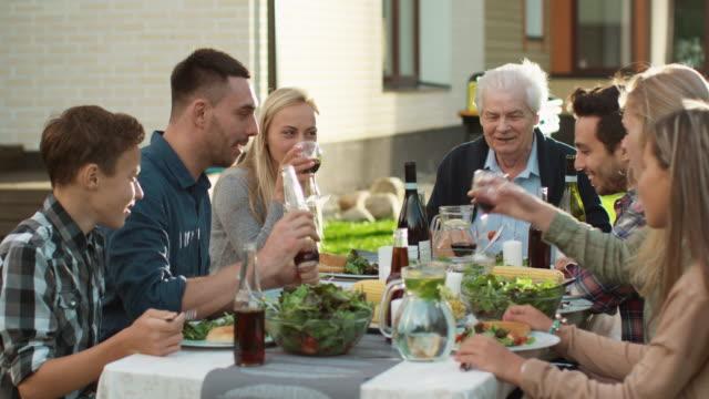 vídeos y material grabado en eventos de stock de grupo de raza mixta gente divirtiéndose, comunicándose y comiendo en la cena familiar al aire libre - árboles genealógicos