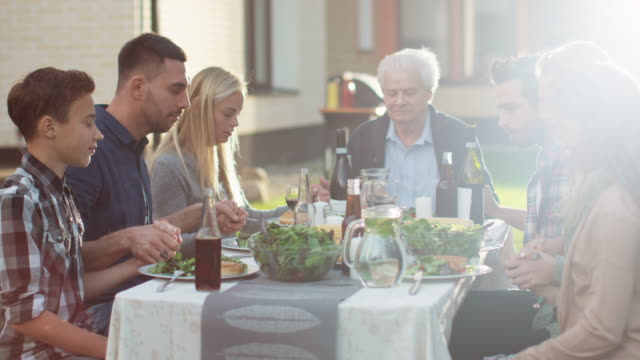 vídeos de stock, filmes e b-roll de grupo de povos da raça misturada que unir as mãos e começar a orar antes do jantar da família - países bálticos