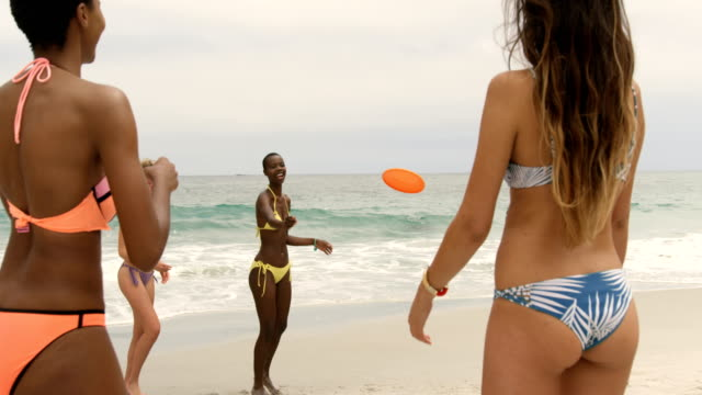 Group of mixed-race female friends playing flying disc on the beach 4k