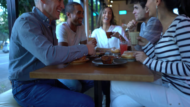 group of multi ethnic friends enjoying breakfast with sweet pastry, coffee and juice talking and having a nice time - cucina francese video stock e b–roll