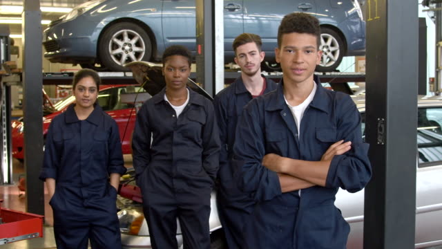 Group of multi racial college apprentices in car workshop wearing boiler suits video