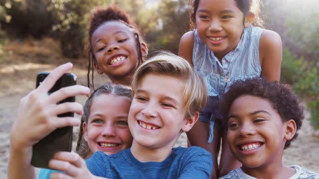 group of multi-cultural children posing for selfie with friends in countryside together - 8 9 anni video stock e b–roll