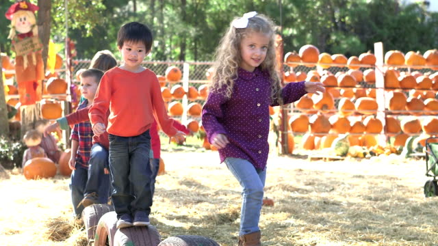 Group of multi-ethnic children at fall festival playing video